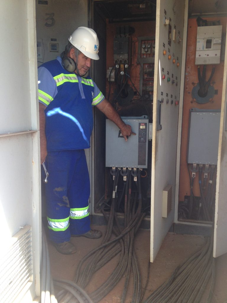Operador da EEAB mostrando para os inspetores da CR, RJ e SINTEC-SP como é realizado a operação do conjunto moto-bomba, com cabos de energia       expostos e porta do painel aberto